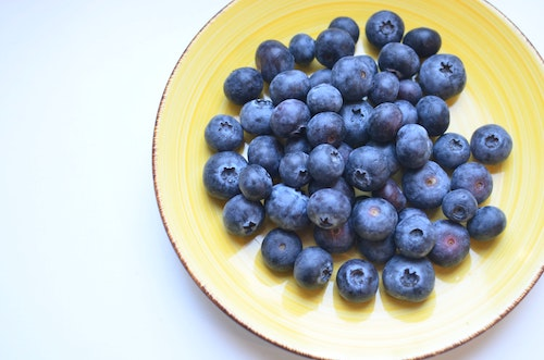 Bright blueberry fruits on a yellow plate from a top view